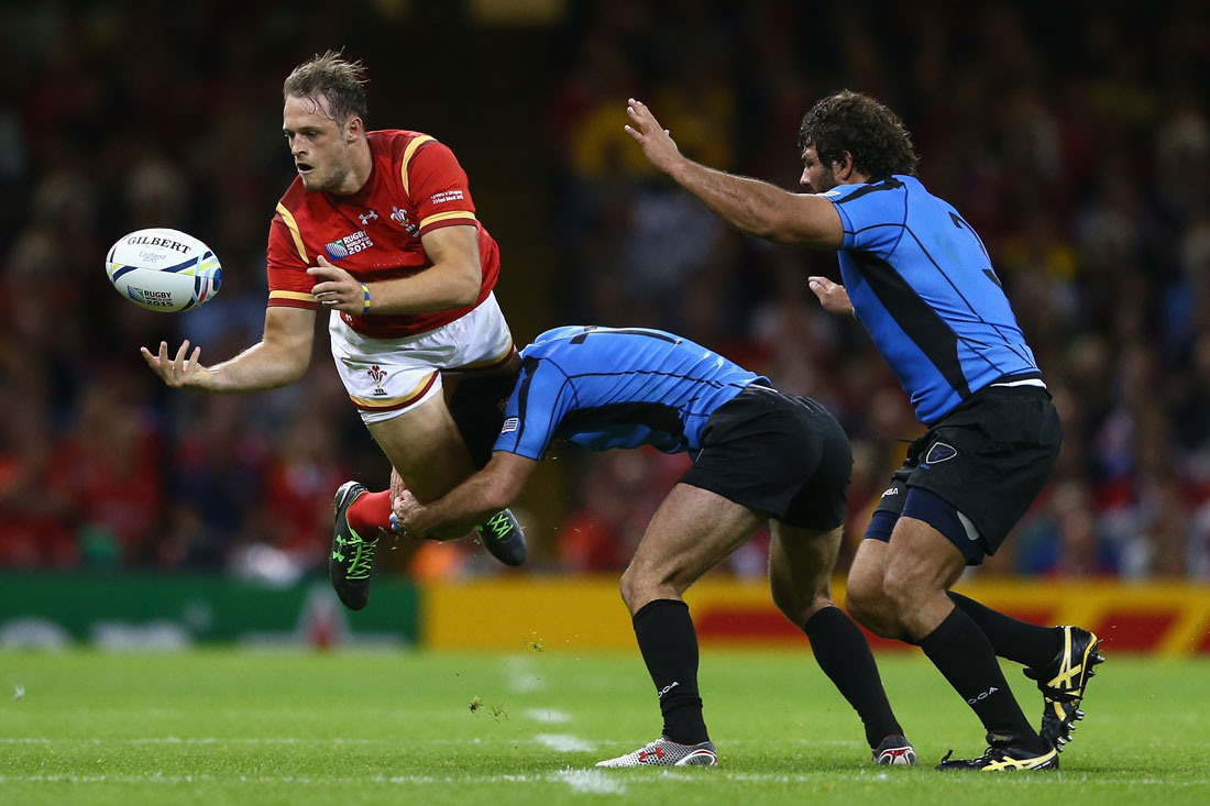 Cory Allen of Wales offloads a pass as he is tackled by Rodrigo Silva of Uruguay, Rugby World Cup, Cardiff, September 2015